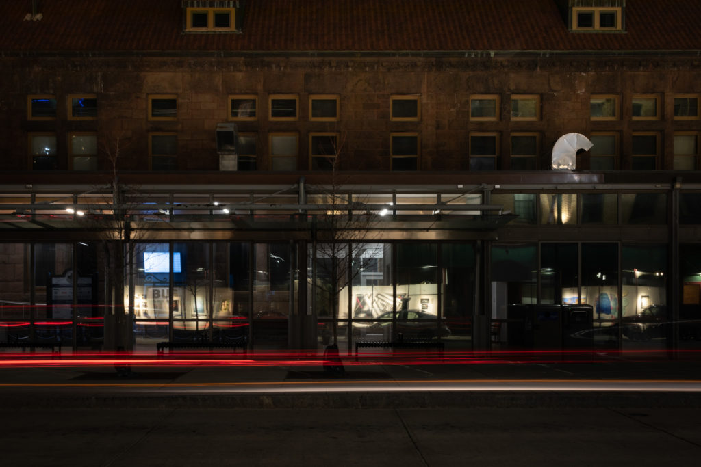 reflection of an art exhibit in the storefront windows of downtown hartford with light trails from a car passing through, photographed by jamie bannon photography.