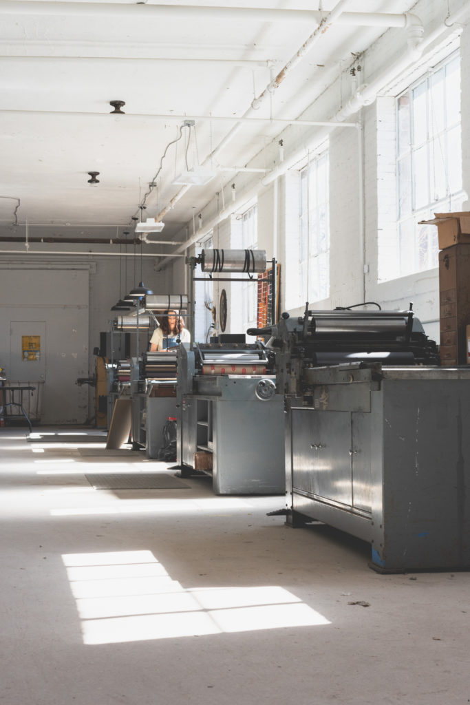 interior of masthay studios, a printmaking studio in west hartford, connecticut, with printer working, photographed by jamie bannon photography.