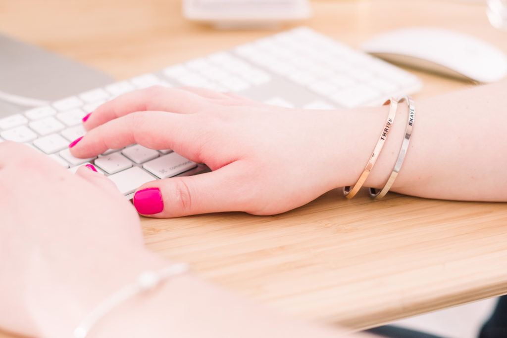 detail of mantra bands on a female entrepreneur's wrist as she types at her computer, as part of a personal branding shoot by jamie bannon photography.