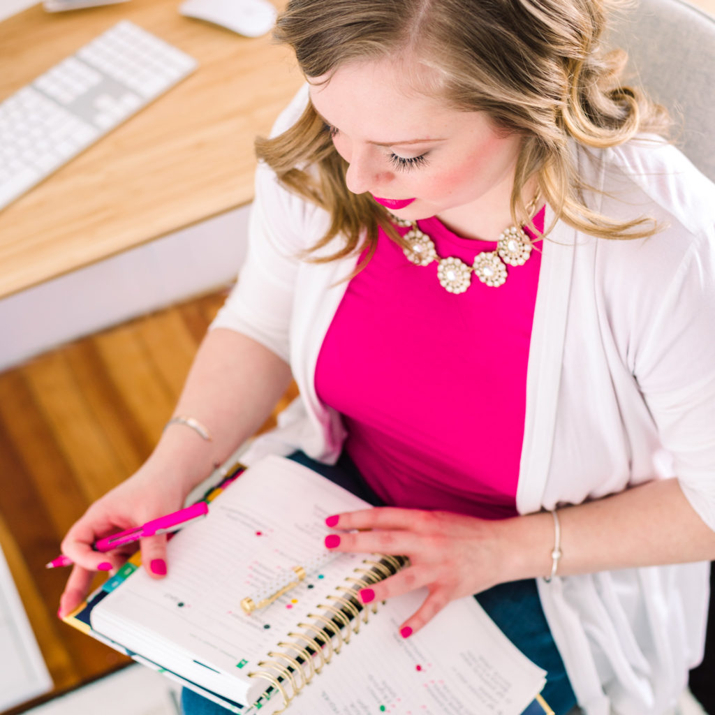 a female entrepreneur looks at her simplified planner, as part of a personal branding shoot by jamie bannon photography.