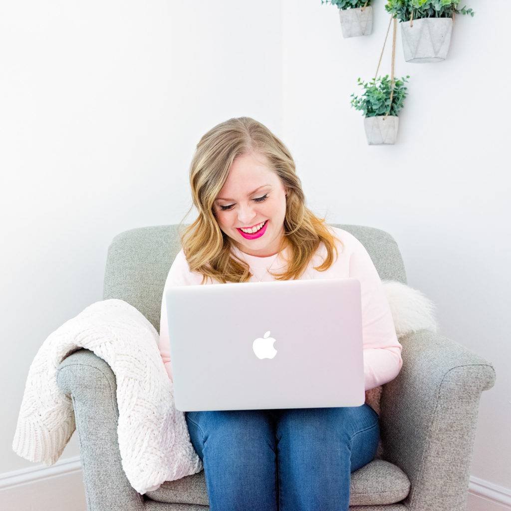 a female entrepreneur works on her laptop in a comfy chair, as part of a personal branding shoot by jamie bannon photography.