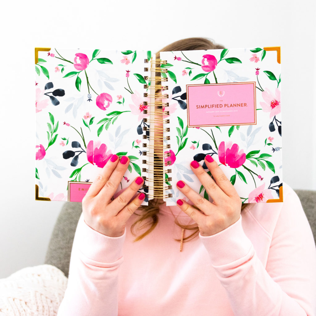 a female entrepreneur holds up her simplified planner, as part of a personal branding shoot by jamie bannon photography.