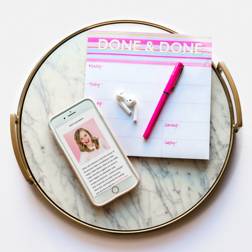 fat lay of an iphone with to-do list, apple ear buds, and a hot pink pen on a marble tray, photographed as part of a business branding shoot by jamie bannon photography.