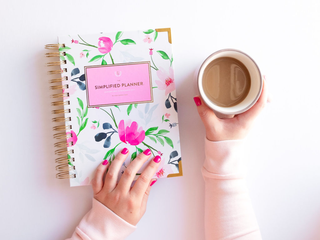 flat lay of a female entrepreneur reaching for her simplified planner and cup of coffee, photographed as part of a personal branding shoot by jamie bannon photography.