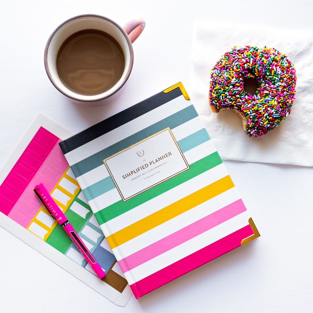 flat lay of a colorful simplified planner, cup of coffee, and chocolate frosted doughnut with rainbow sprinkles, as part of a personal branding shoot by jamie bannon photography.