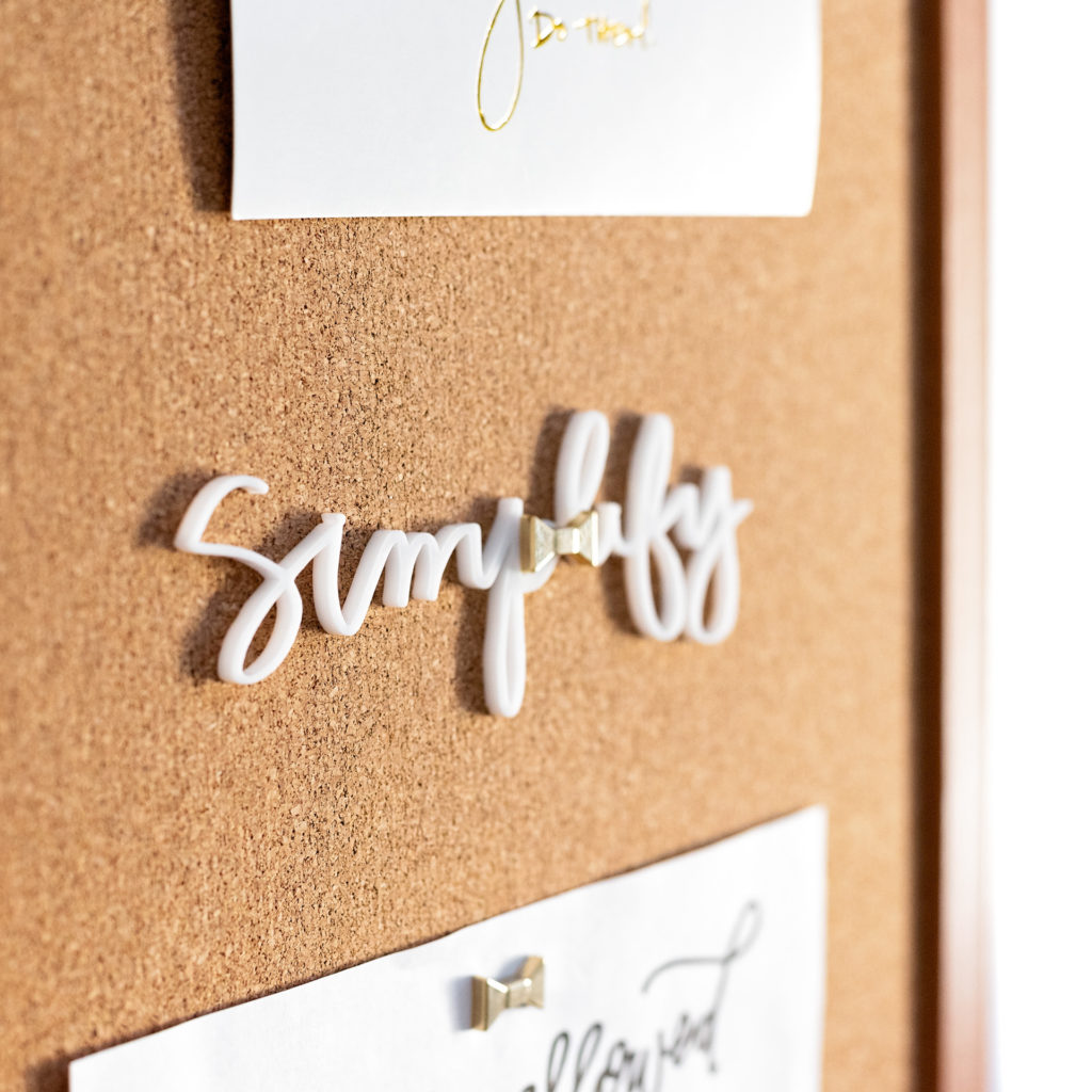 "the word ""simplify"" pinned to a cork board, photographed as part of a personal branding shoot by jamie bannon photography."