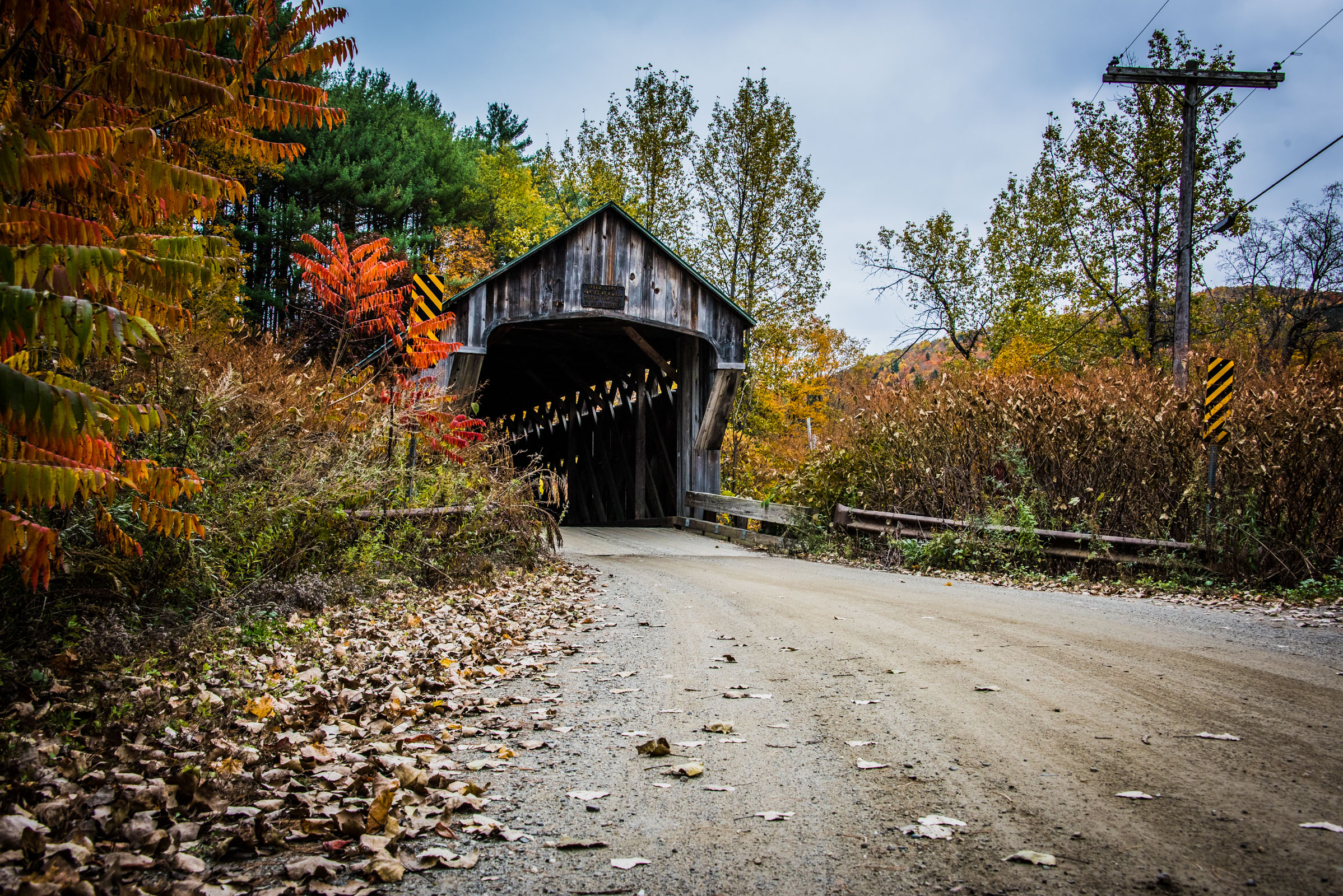 a dirt road leads to a covered bridge surrounded by colorful leaves in vermont, photographed by jamie bannon photography.