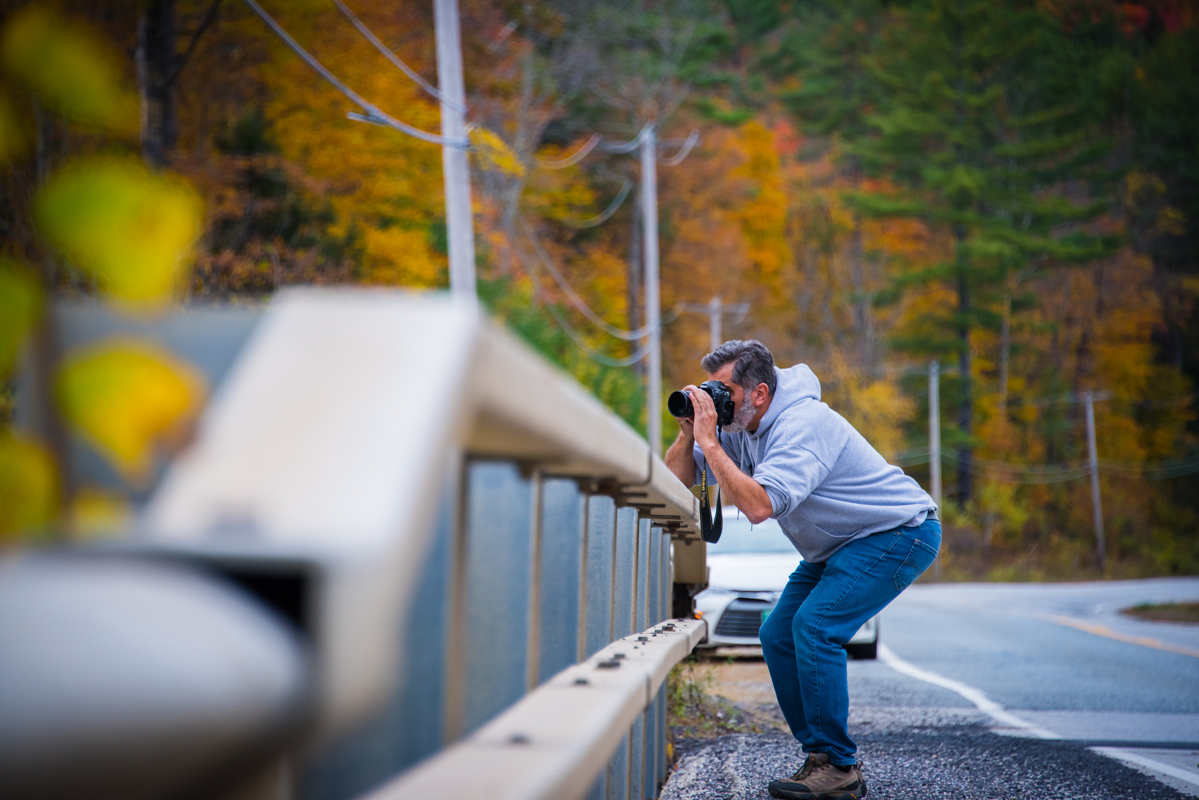 portrait of a photographer shooting a colorful fall landscape in vermont, photographed by jamie bannon photography.