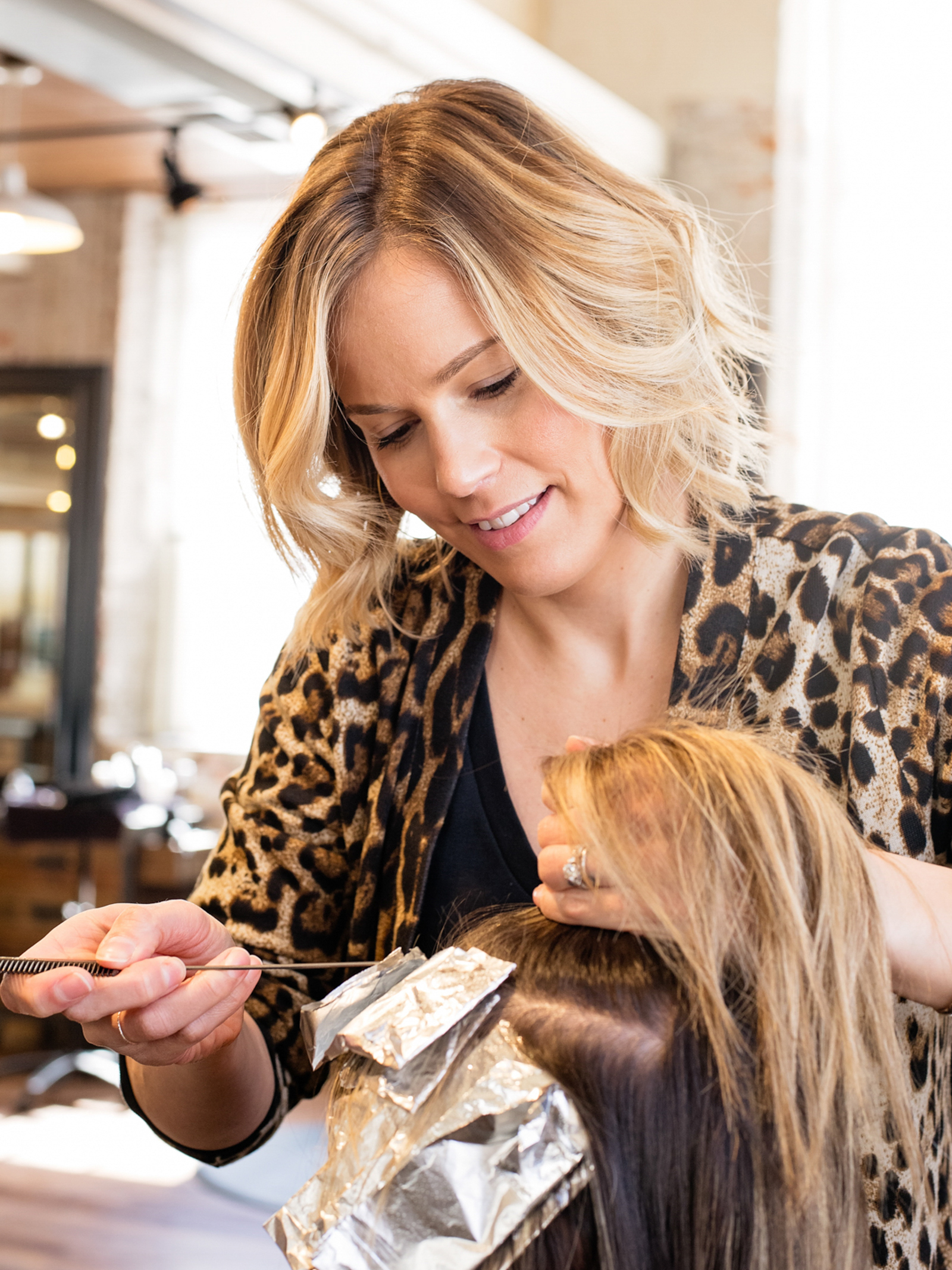 a salon hair stylist gives a woman highlights, photographed by jamie bannon photography.