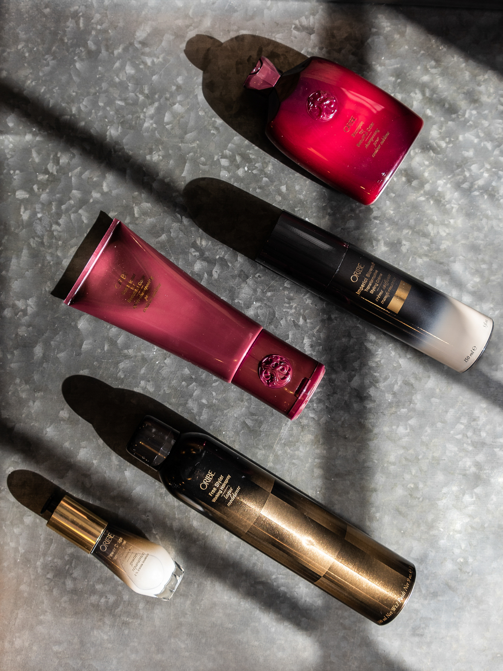 a dramatically lit flat lay of oribe hair products at a salon, photographed by jamie bannon photography.