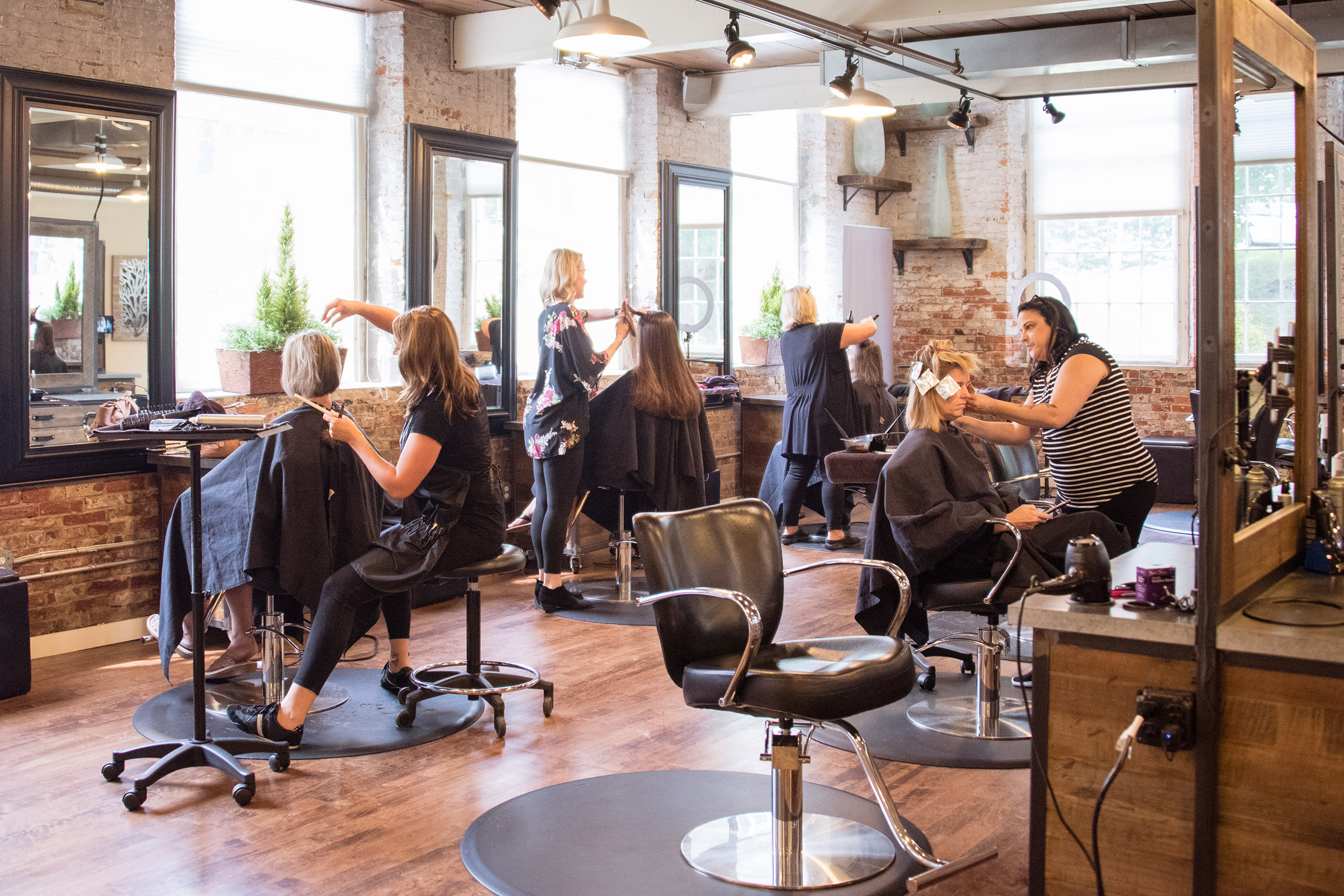 interior overview of a busy salon with stylists working, photographed by jamie bannon photography.