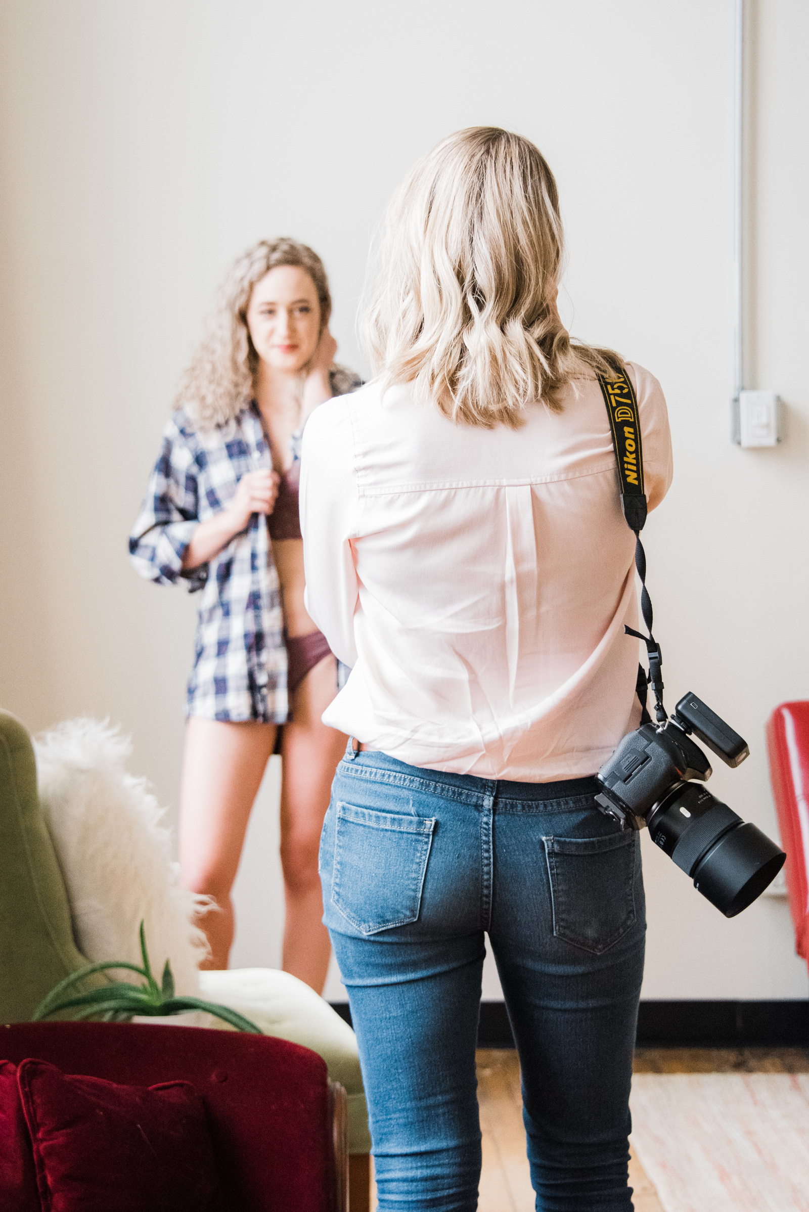 a boudoir photographer poses her client, photographed as part of a behind the scenes brand shoot by jamie bannon photography.