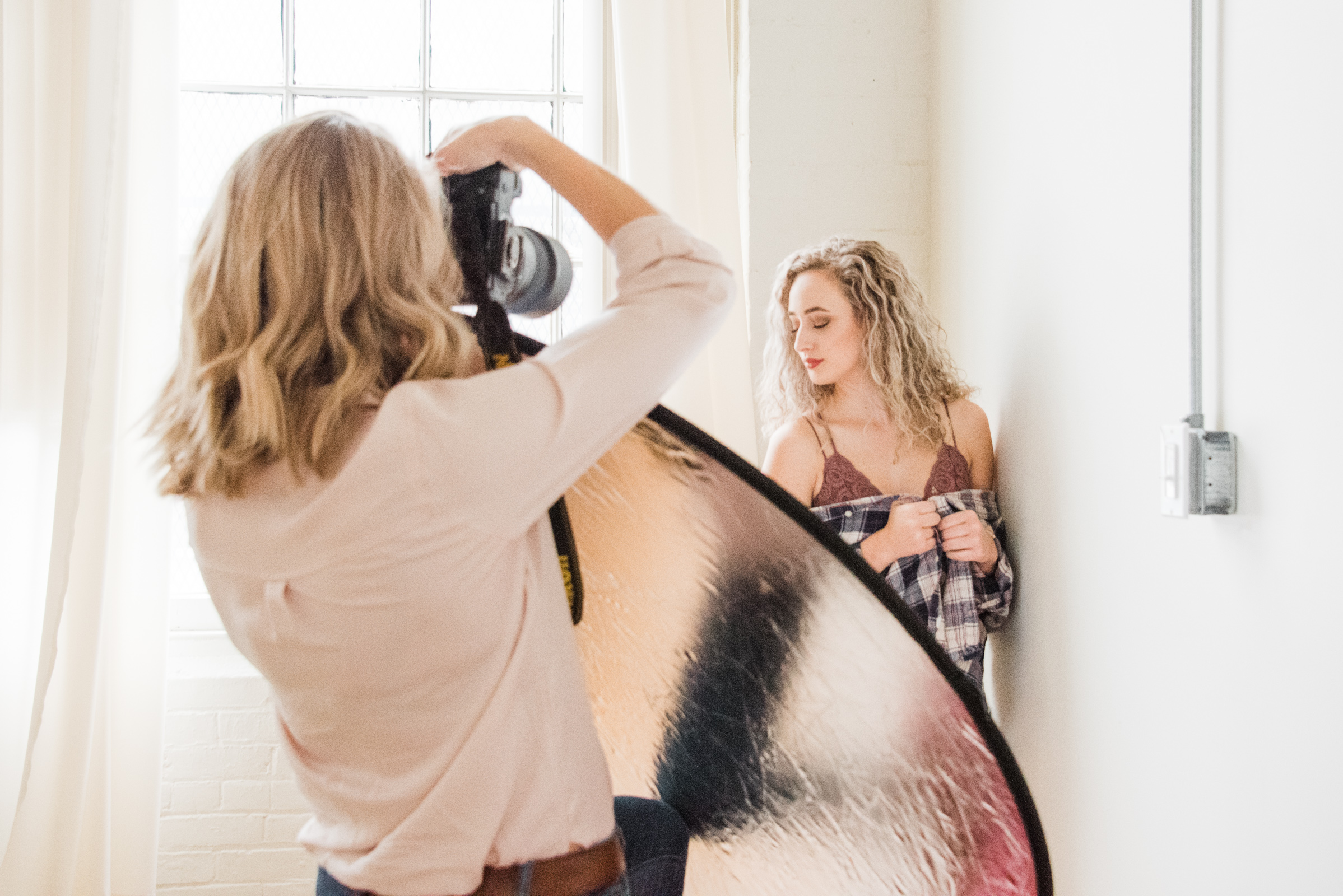 a boudoir photographer photographs her client, photographed as part of a behind the scenes brand shoot by jamie bannon photography.