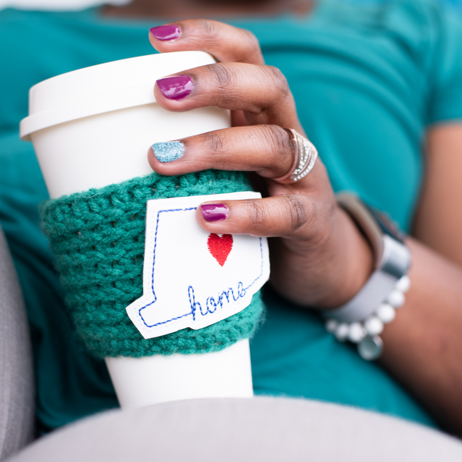 detail of a crochet artist sipping coffee using one of her creations, photographed as part of a brand shoot by jamie bannon photography.