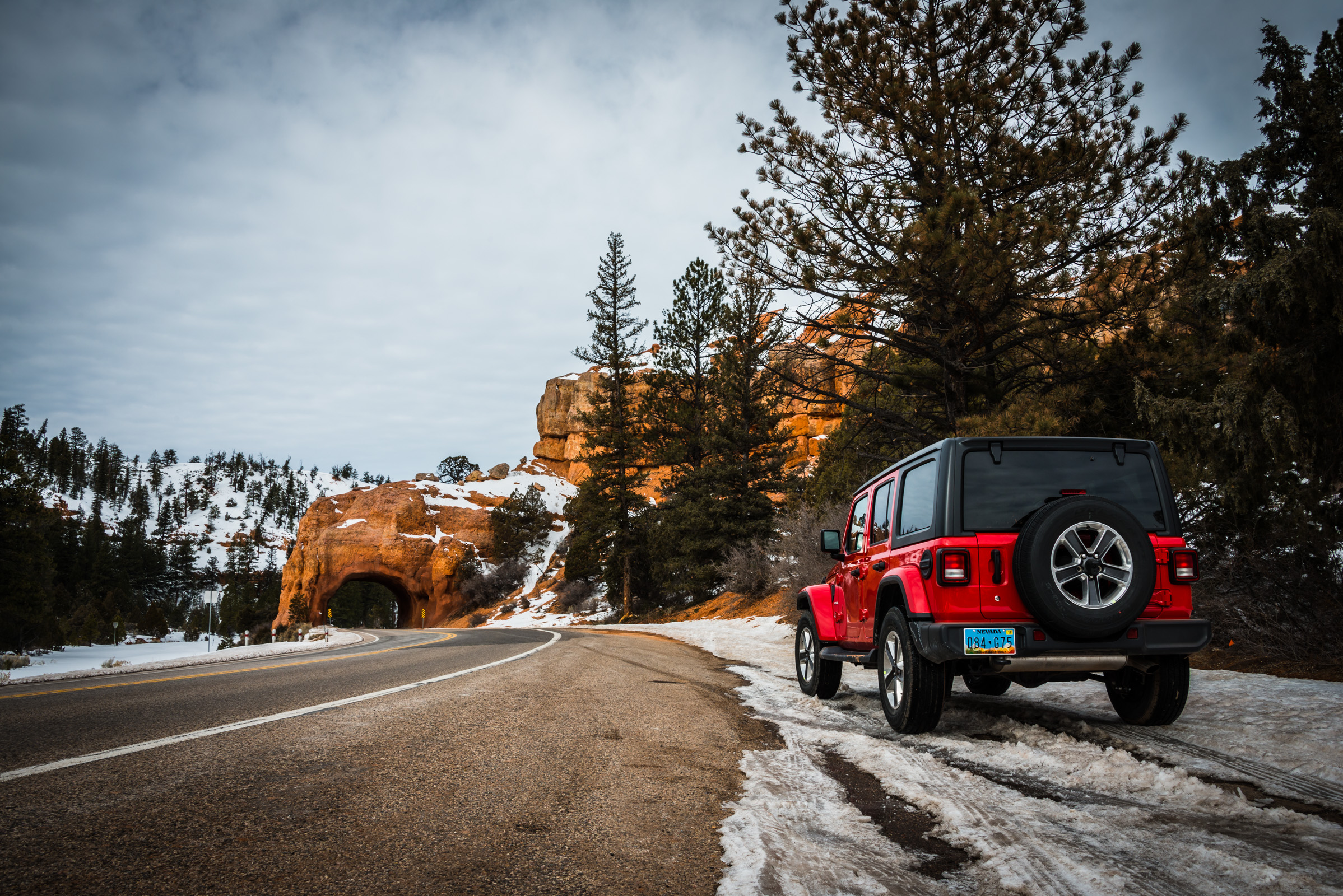 roadside landscape with a jeep wrangler and red rocks in the snow, somewhere between utah and nevada, photographed by jamie bannon photography.