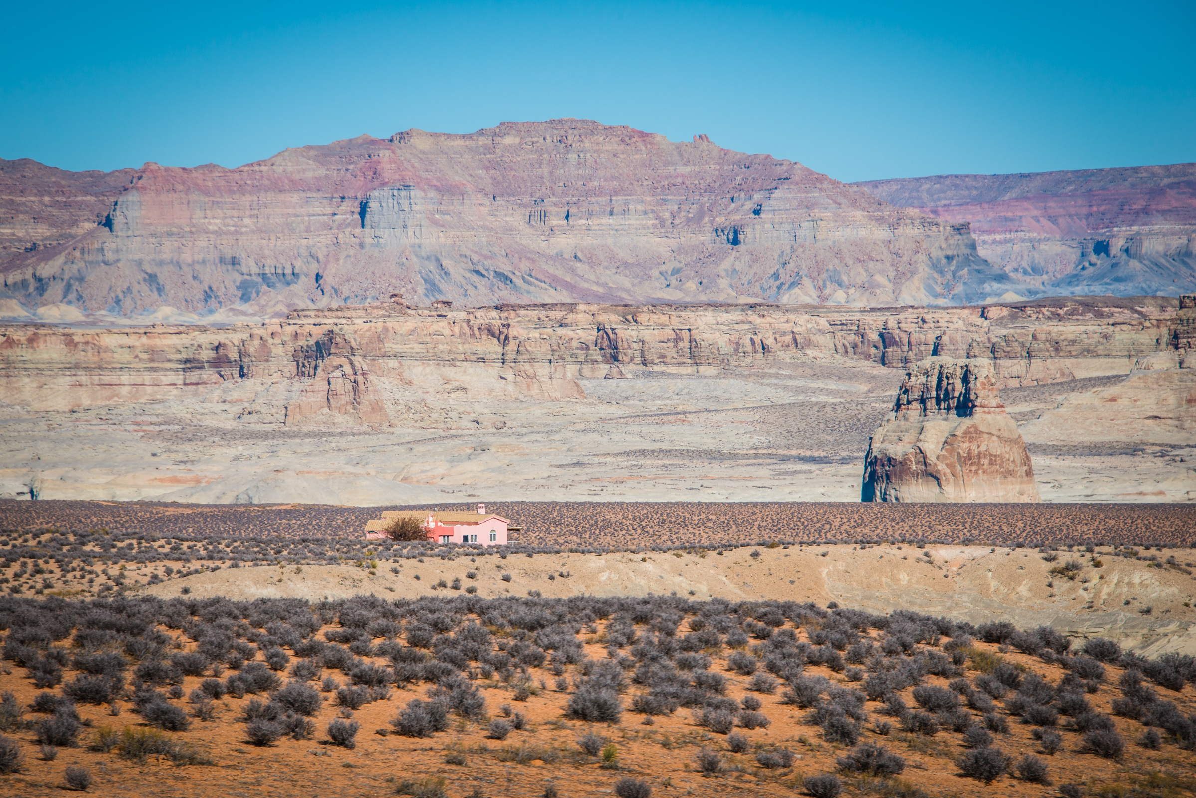 roadside landscape with a pink house surrounded by bluffs, somewhere between utah and nevada, photographed by jamie bannon photography.