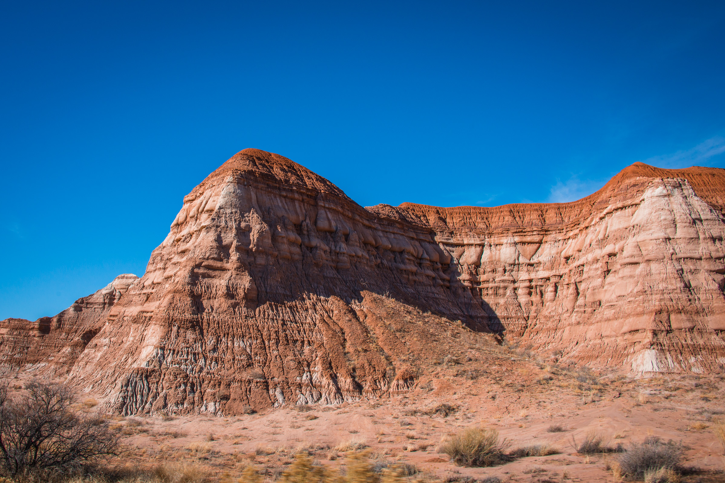 roadside landscape with red rocks against a blue sky somewhere between utah and nevada, photographed by jamie bannon photography.
