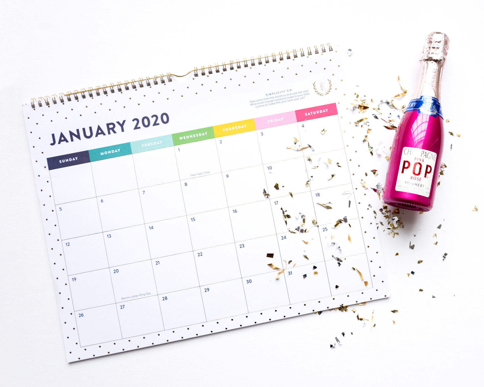flat lay with a january calendar page, a bottle of champagne, and confetti, photographed by jamie bannon photography.