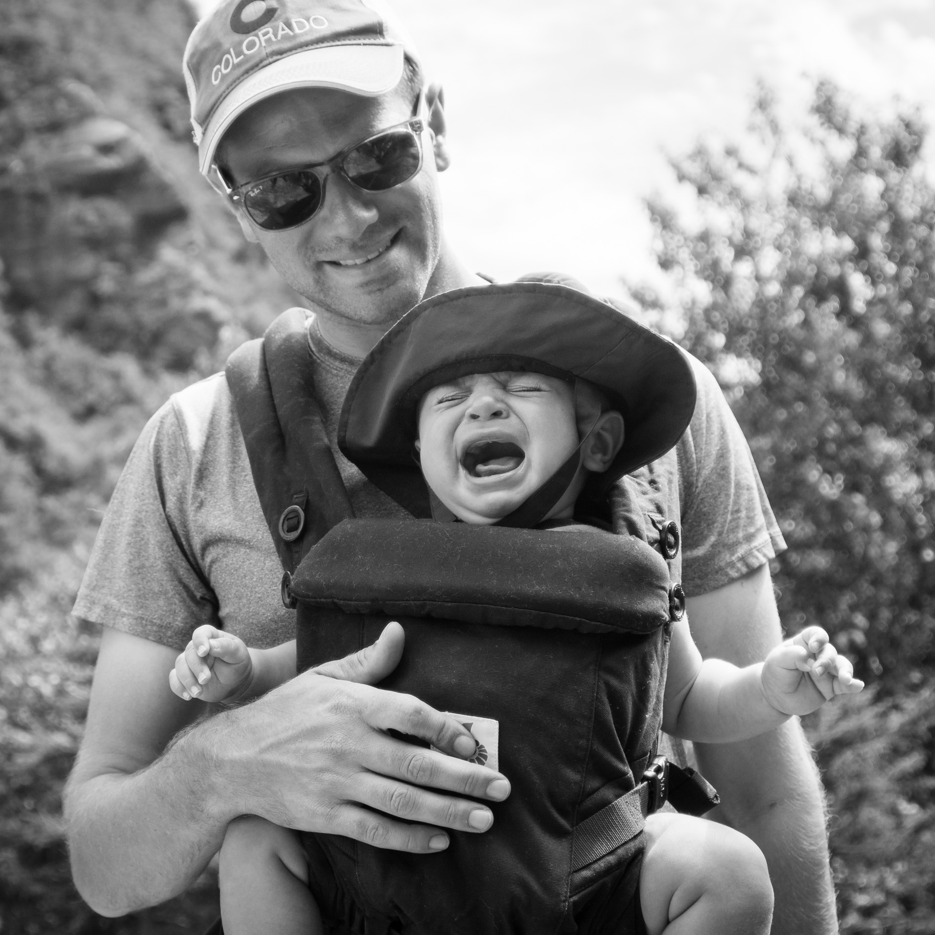 a baby cries on a hike while carried by his dad, photographed by jamie bannon photography.