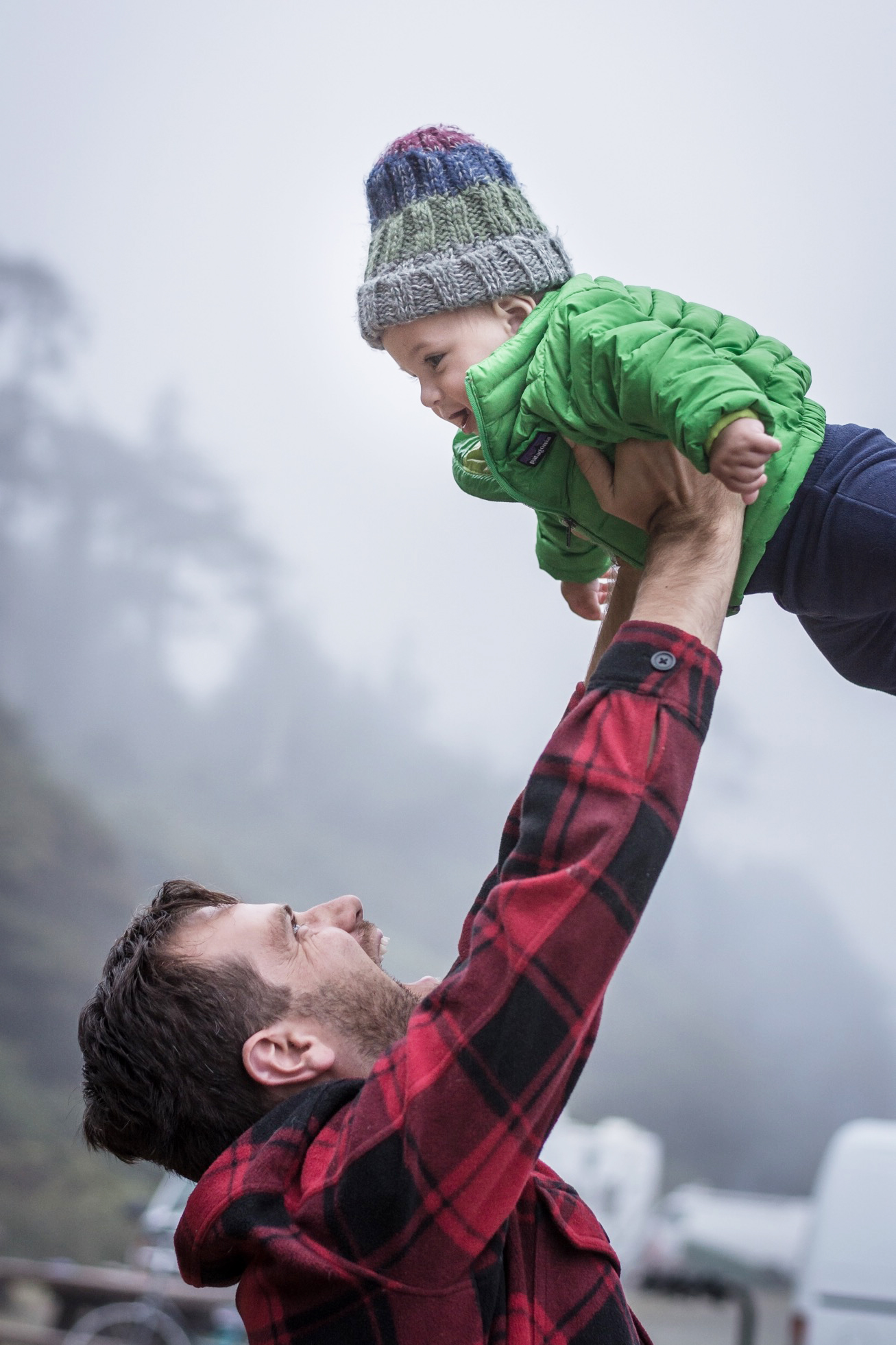 a dad plays with his baby on a foggy evening on the olympic peninsula, photographed by jamie bannon photography.