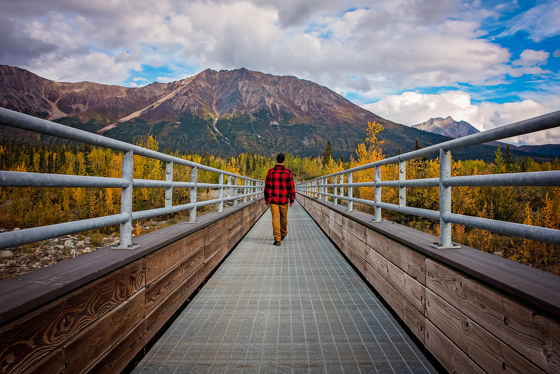 a man walks across a footbridge in mccarthy, alaska, photographed by jamie bannon photography.