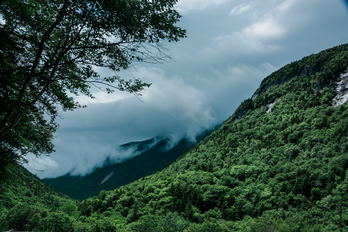 clouds hang low over the white mountains on a rainy day in new hampshire, photographed by jamie bannon photography.