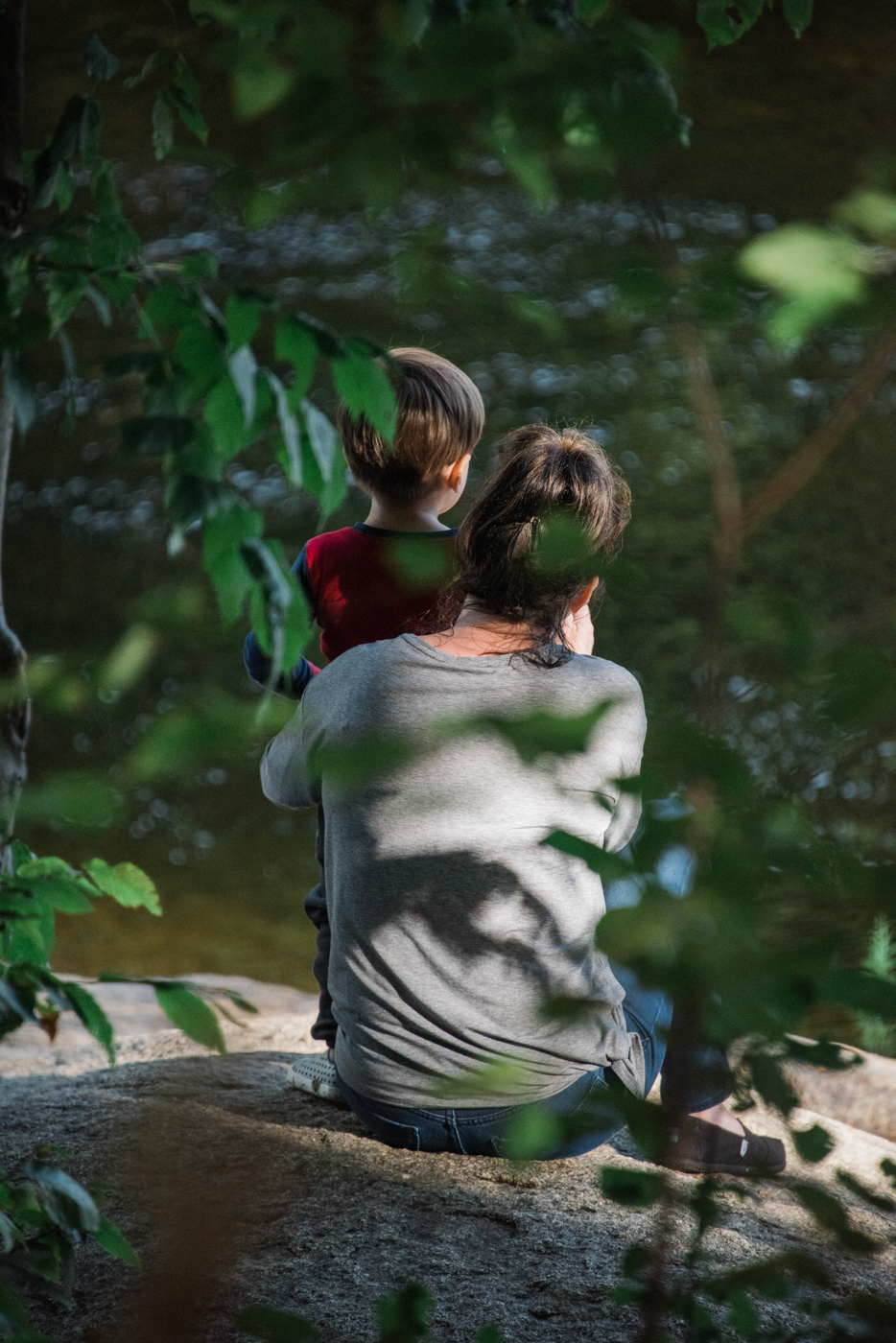 grandma and grandson sit by the pemigewasset river in new hampshire, photographed by jamie bannon photography.