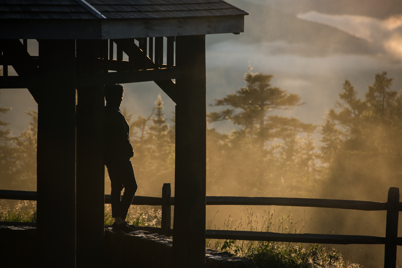 a woman admires the sunset off the kancamagus highway in the white mountains, new hampshire, photographed by jamie bannon photography.