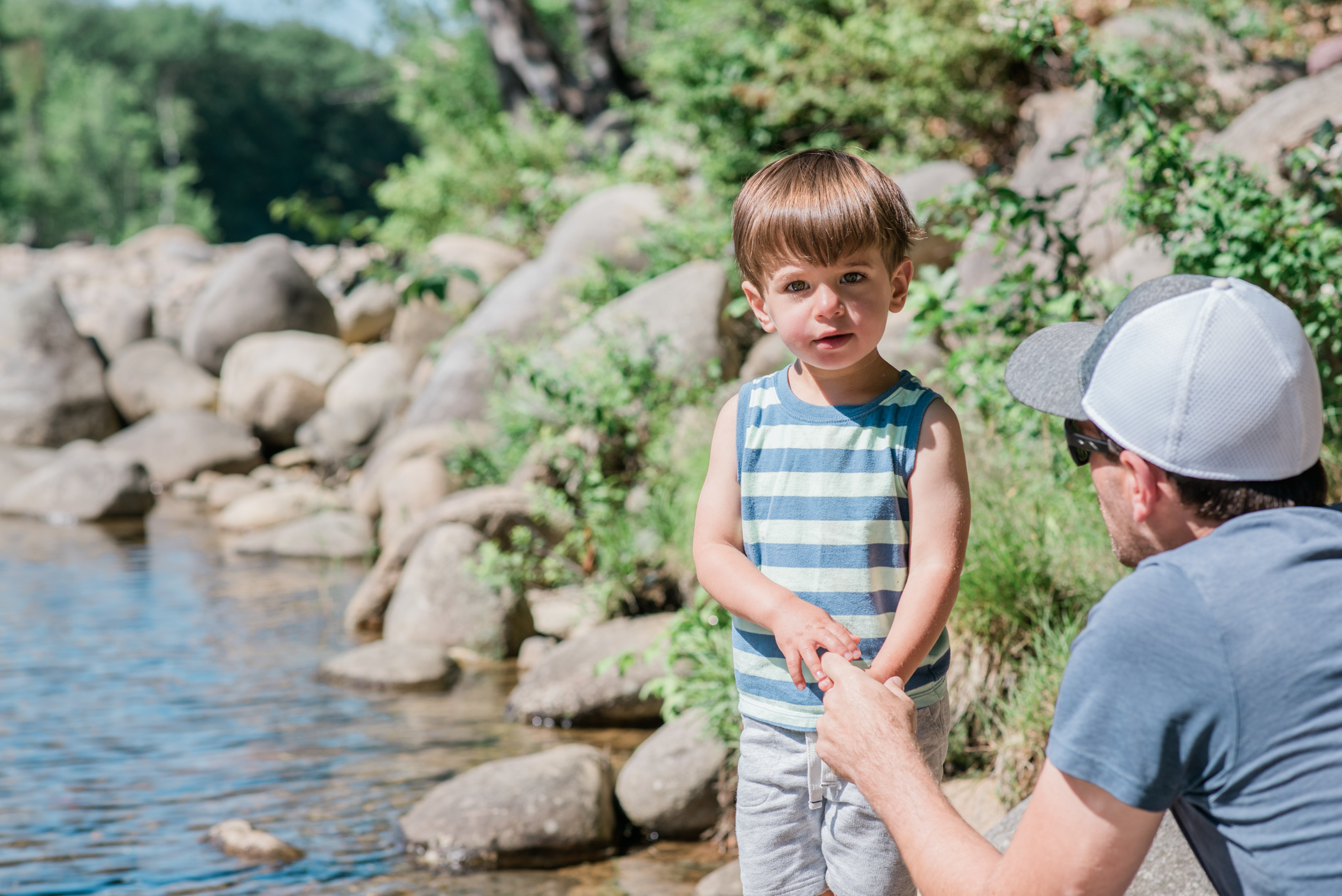 a little boy and his dad look for tadpoles in the pemigewasset river in the white mountains, new hampshire, photographed by jamie bannon photography.
